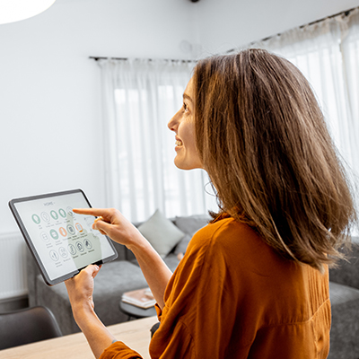 Young woman controlling home light with a digital tablet in the living room.