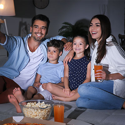 family relaxing in smart home watching the tv on the sofa at night.