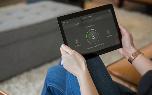 Young woman using smart home security access control system on her tablet.
